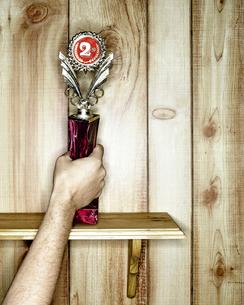 Hand taking trophy off shelfの写真素材 [FYI01983397]