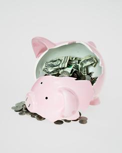 Broken piggy bank and money spilling outの写真素材 [FYI01983402]
