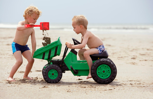 Boys playing with toy digger on beachの写真素材 [FYI01983408]