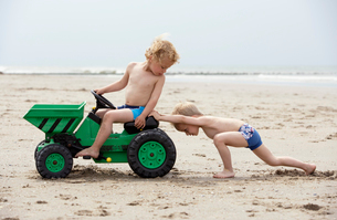 Boys playing with toy digger on beachの写真素材 [FYI01983464]