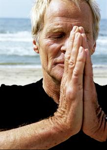 Senior man praying on beachの写真素材 [FYI01983524]