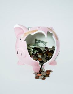 Broken piggy bank and money spilling outの写真素材 [FYI01983537]