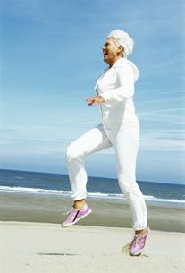 Senior woman skipping on beachの写真素材 [FYI01983545]
