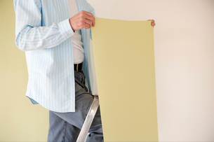 Man putting up wallpaperの写真素材 [FYI01983669]