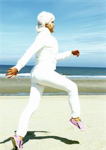 Senior woman skipping on beachの写真素材 [FYI01983674]