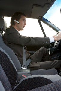 man wearing hands-free device in a carの写真素材 [FYI01983865]