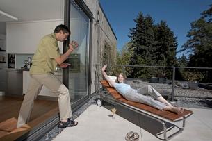 Man videotaping woman on lounge chairの写真素材 [FYI01984030]