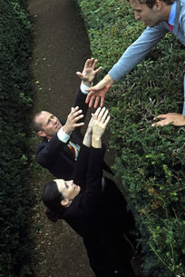 Man and Woman reaching help over a hedgeの写真素材 [FYI01984243]