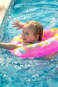 Girl in swimming pool using inner tubeの写真素材 [FYI01984273]