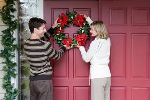 Couple hanging Christmas wreathの写真素材 [FYI01984311]