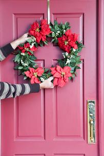 Person hanging Christmas wreathの写真素材 [FYI01984318]