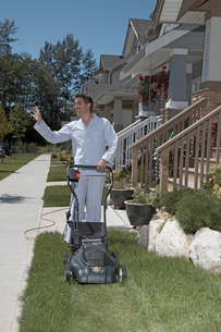 Young man mowing lawn in pajamasの写真素材 [FYI01984322]