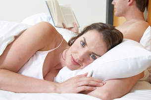 Young woman in bed beside her husbandの写真素材 [FYI01984382]