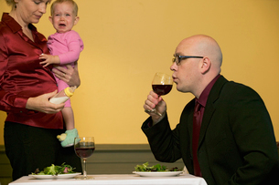 Mother holding baby as husband sips wineの写真素材 [FYI01984484]
