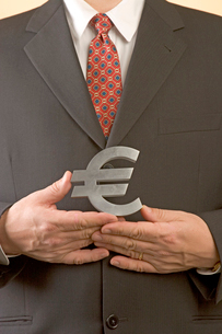 Businessman holding silver Euro signの写真素材 [FYI01984493]
