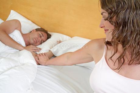 Young woman touching sleeping husbandの写真素材 [FYI01984516]
