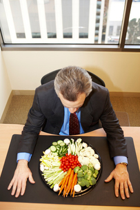 Businessman with tray of vegetablesの写真素材 [FYI01984629]