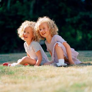 Twin girls laughing outdoorsの写真素材 [FYI01984638]