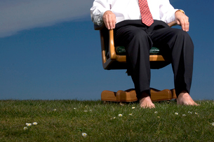 Barefoot man sitting in chair outdoorsの写真素材 [FYI01984676]