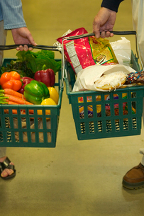 People holding grocery basketsの写真素材 [FYI01984682]