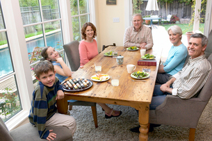 Family sitting at dinner tableの写真素材 [FYI01984712]