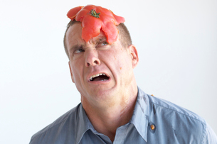 Man with smashed tomato on headの写真素材 [FYI01984729]