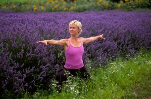 Woman in yoga pose near lavender fieldの写真素材 [FYI01984776]