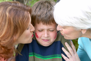 Mother and grandmother kissing a boyの写真素材 [FYI01984789]
