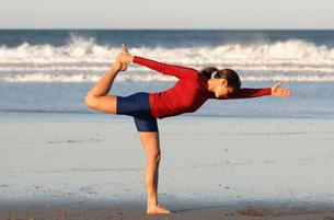 Asian woman in yoga pose on beachの写真素材 [FYI01984791]