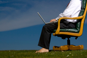 Barefoot man sitting in chair outdoorsの写真素材 [FYI01984861]