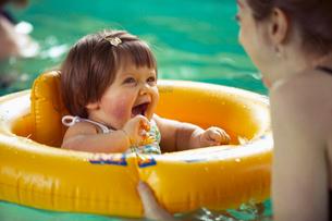 Baby girl using inner tube in poolの写真素材 [FYI01984878]