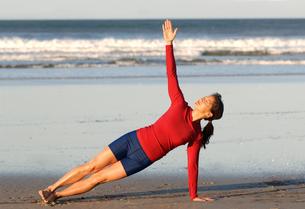 Asian woman in yoga pose on beachの写真素材 [FYI01984912]