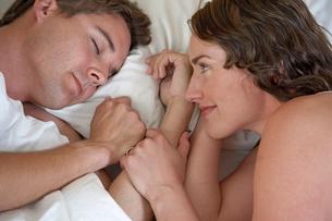 Young woman watching sleeping husbandの写真素材 [FYI01984924]