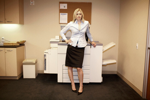 Businesswoman standing by copy machineの写真素材 [FYI01985068]