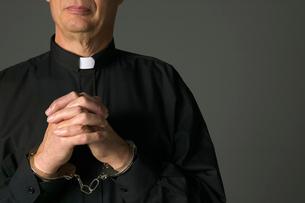 Priest in handcuffs prayingの写真素材 [FYI01985069]