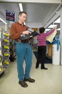 Man examining power tool in a storeの写真素材 [FYI01985121]