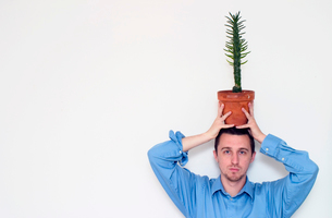 Man holding potted plant on his headの写真素材 [FYI01985165]