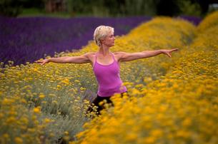 Woman in yoga pose among flowersの写真素材 [FYI01985206]