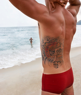 Young man with tattoo on beachの写真素材 [FYI01985259]