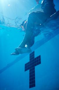 woman dangling feet in swimming poolの写真素材 [FYI01985285]