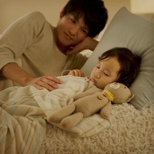 ベッドで眠る女の子と父親の写真素材 [FYI01985351]