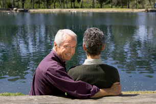 Senior couple sitting by pondの写真素材 [FYI01985381]