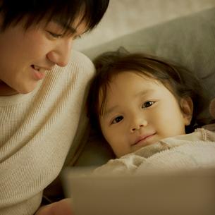 ベッドで絵本の読み聞かせをする親子の写真素材 [FYI01985418]