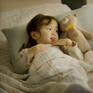 クマのぬいぐるみを見る女の子の写真素材 [FYI01985427]