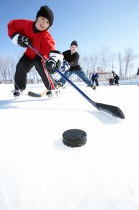 Ice hockey player skating towards puckの写真素材 [FYI01985433]