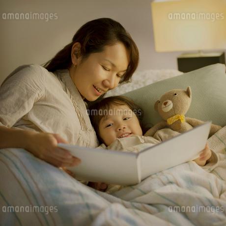 ベッドで絵本の読み聞かせをする親子の写真素材 [FYI01985442]
