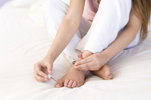 young woman painting toe nails on bedの写真素材 [FYI01985470]