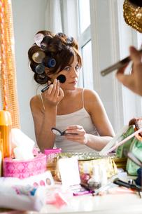 Woman applying makeup wearing curlersの写真素材 [FYI01985484]