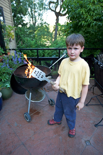 Young boy grilling in backyardの写真素材 [FYI01985487]