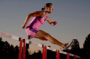 Female athlete jumping over hurdlesの写真素材 [FYI01985556]